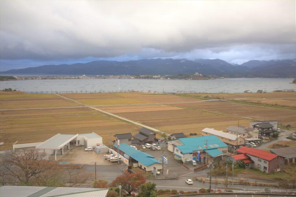 Vue sur les champs et le lac Kamo depuis le Ryotsu Yamaki Hotel