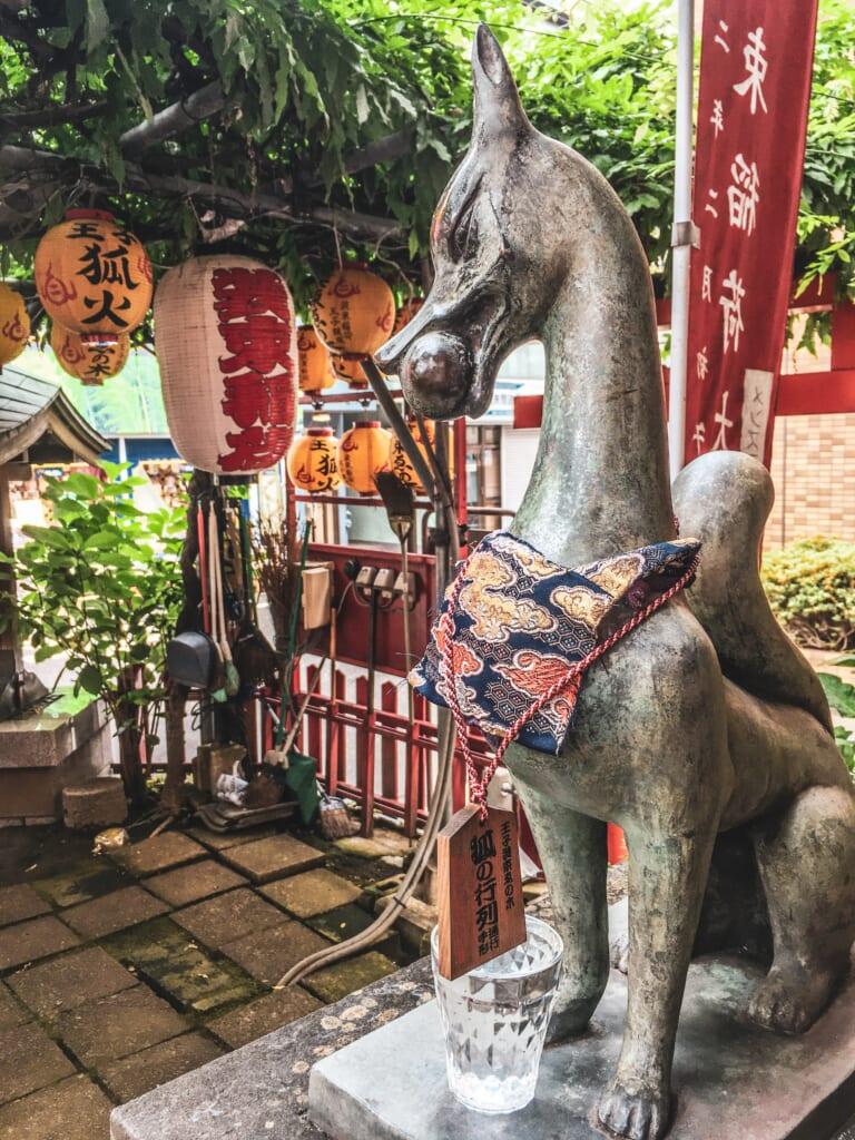 Statue de renard au sanctuaire Shozoku Inari Jinja, à l'emplacement où l'énoki était initialement situé.