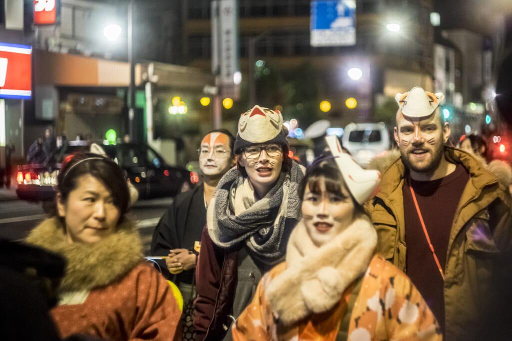 des étrangers participant à la parade du nouvel an japonais en l'honneur du dieu renard inari