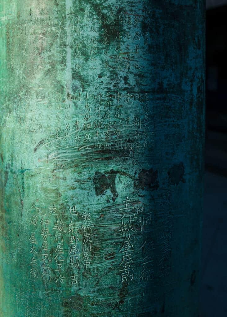 inscriptions en kanji sur un torii en bronze