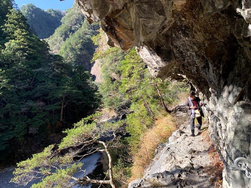 Homme marchant sur un sentier de montagne à flanc de montagne, en se tenant à une chaîne