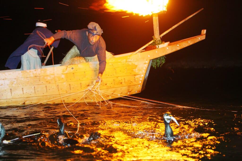 Japonais pratiquand la pêche traditionnelle au cormoran la nuit, à la lumière d'un feu
