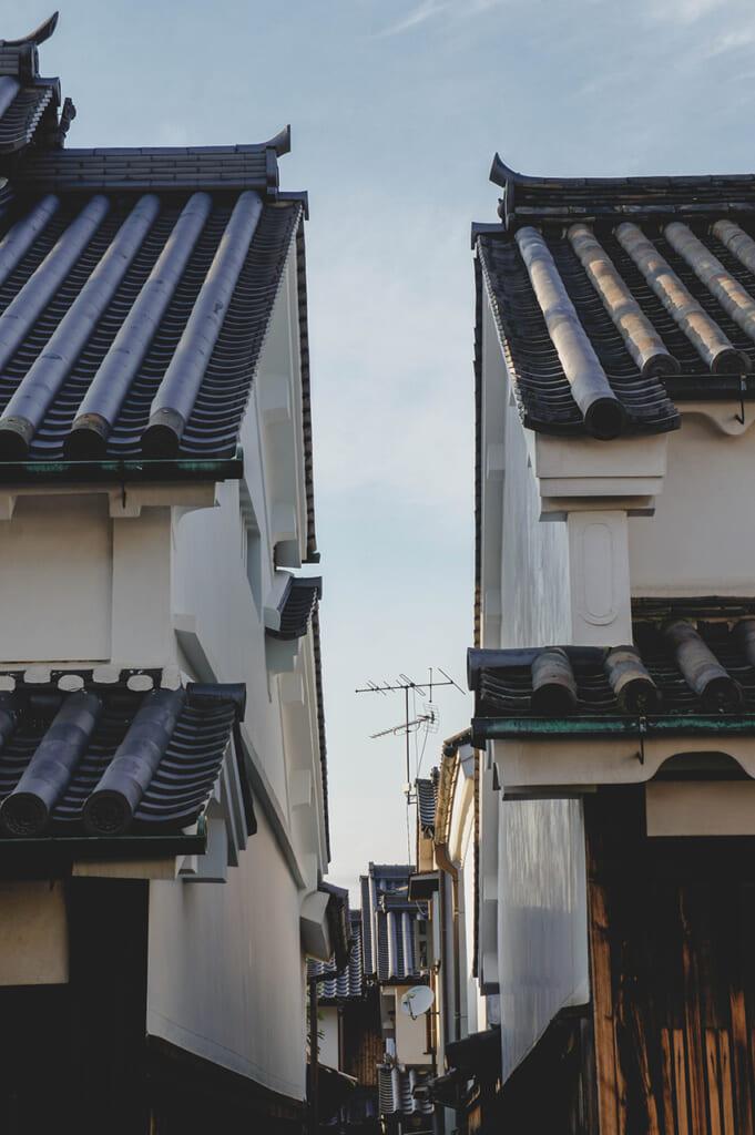 Deux maisons japonaises traditionnelles aux toits de tuiles séparées par une ruelle étroite