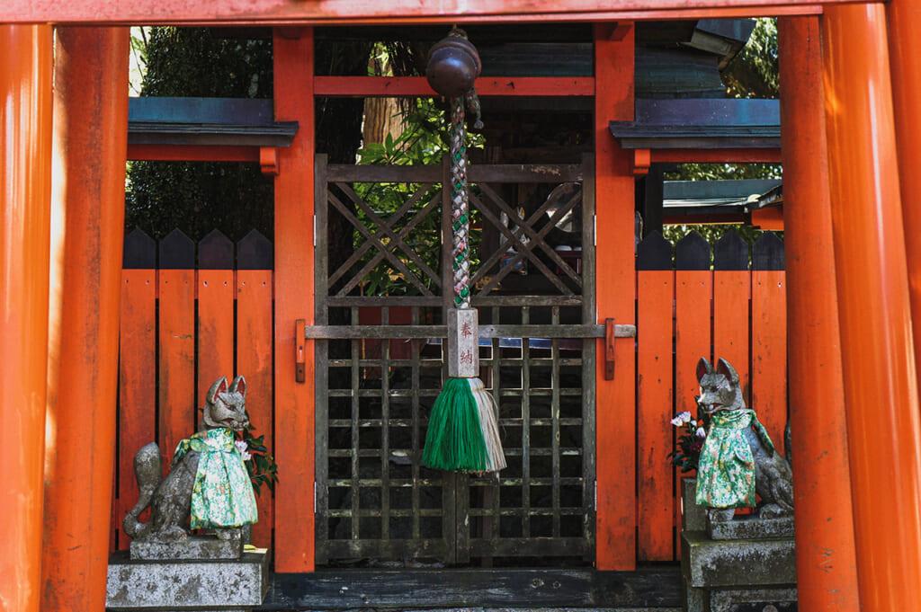 Un sanctuaire inari avec ses torii vermillon et ses statues de renards