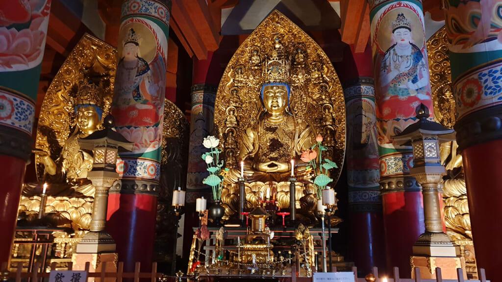 Statues bouddhistes japonaises dorées au milieu de colonnes peintes