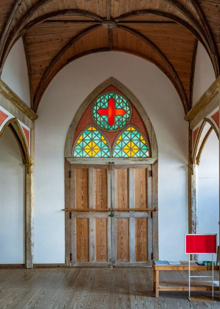 Porte d'entrée de l'église de Gorin surmontée d'un vitrail coloré
