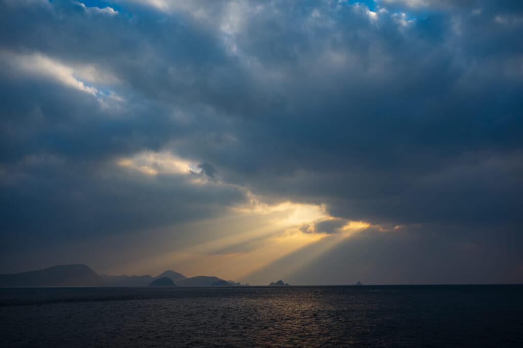 Rayons de soleil perçant les nuages au petit matin sur la mer des îles Goto