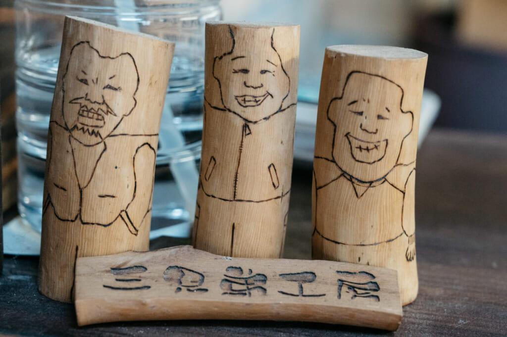 Illustrations pyrogravées sur du bois de camélia, représentant les trois fondateurs de Sankyodai Kobo