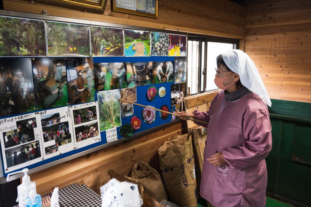 Productrice de tsubaki expliquant le processus traditionnel de production d'huile de camélia