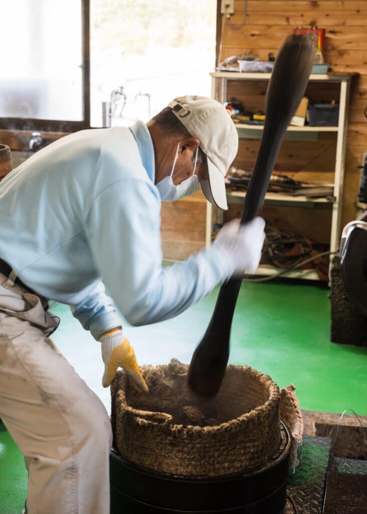 Producteur de tsubaki pilant les graines à l'ancienne