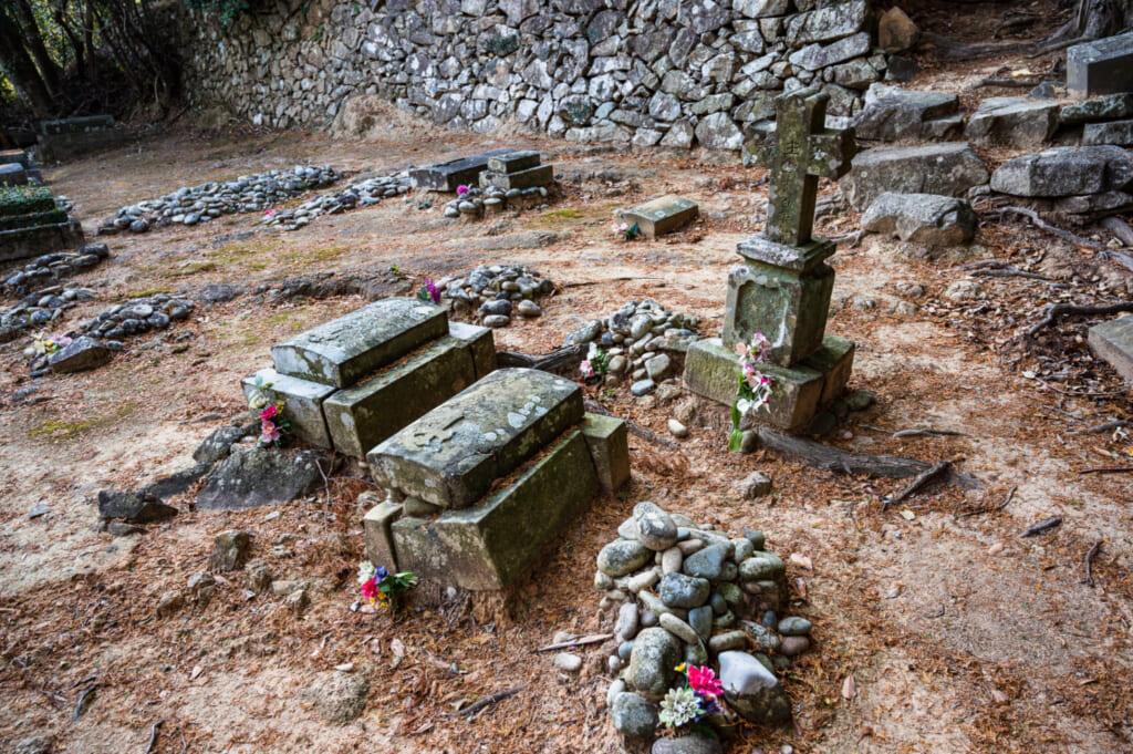 Tombes dans le cimetière chrétien de Hisaka à Goto : tas de pierres pour les chrétiens cachés et croix traditionnelles plus récentes