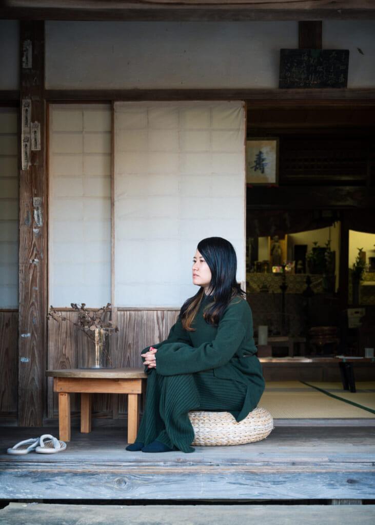 Japonaise assise devant les portes d'un temple rural
