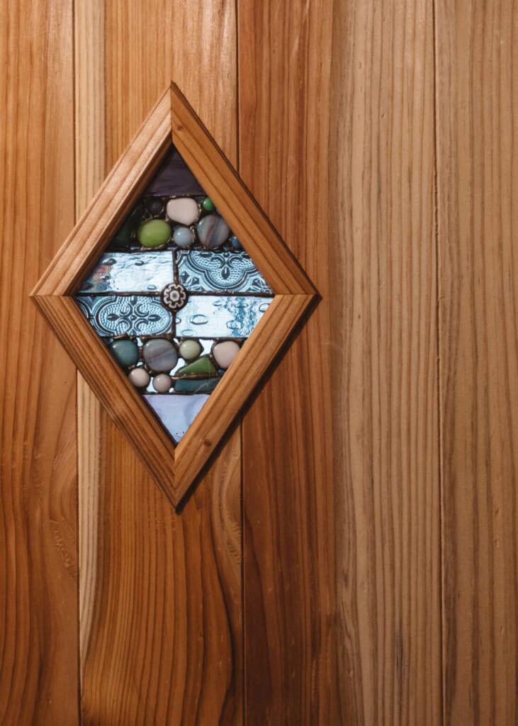 Petit vitrail en forme de losange incrusté dans une porte en bois
