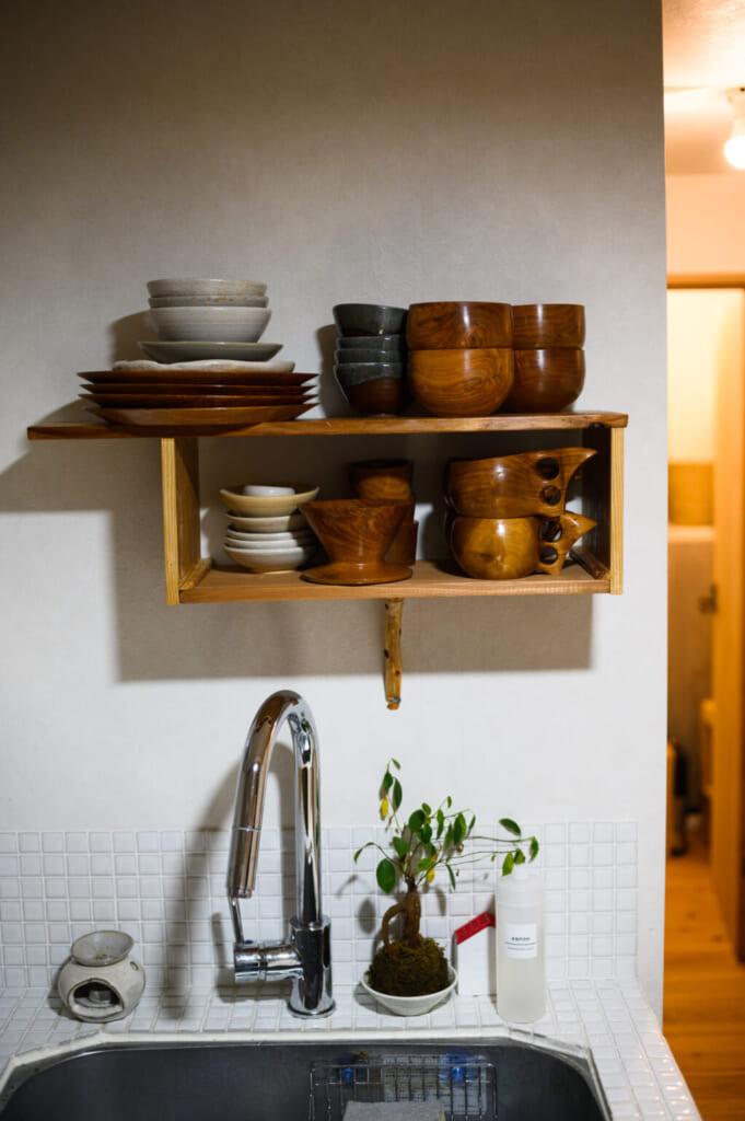 Étagère dans laquelle sont rangés de la vaisselle en bois artisanale au-dessus d'un évier