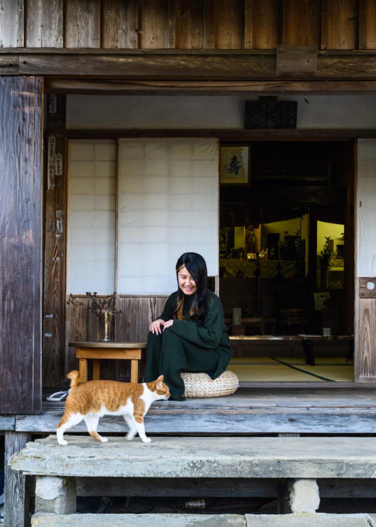 Chat roux et blanc et femme japonaise devant un temple bouddhiste