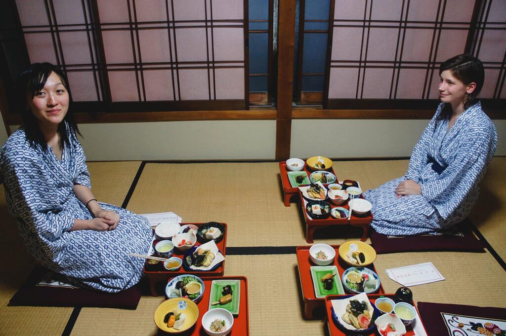 Deux personnes en yukata, devant un repas de shojin ryori servi dans une chambre japonaise