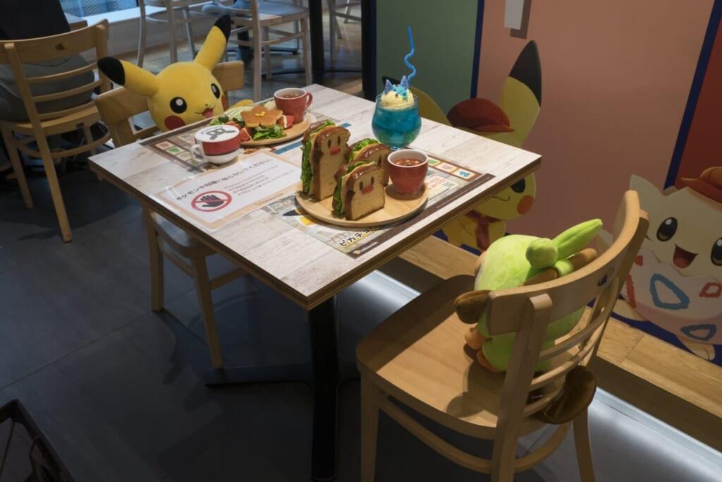 Pokémon installés à une table du Pokémon Café, devant des répliques de plats en plastique