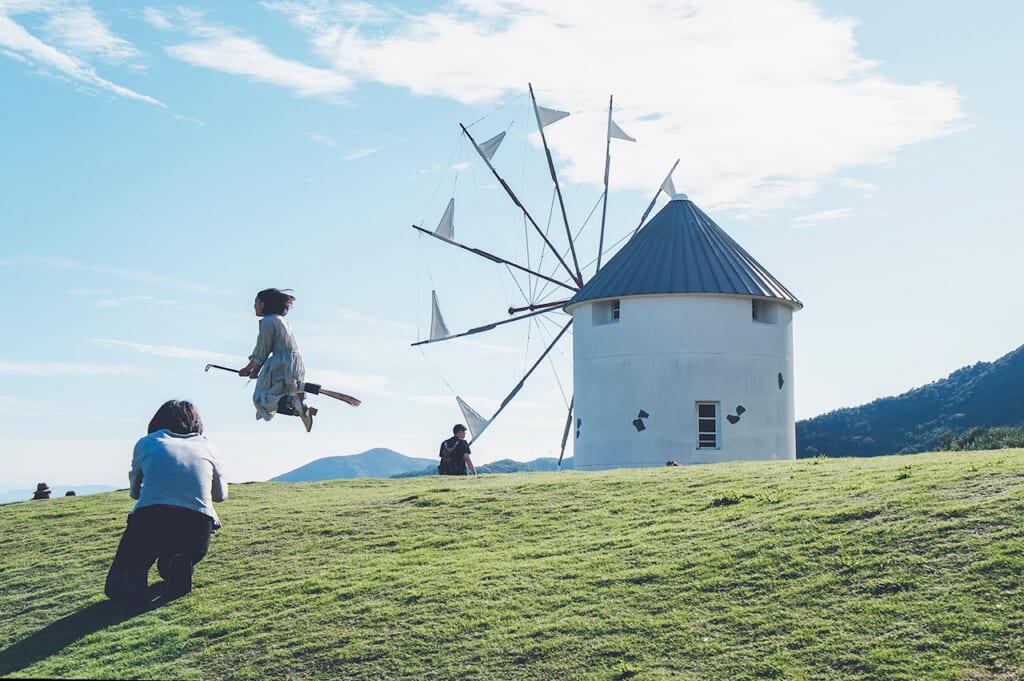 Moulin grec sur l'île de Shodoshima devant lequel une jeune fille semble voler sur un balais