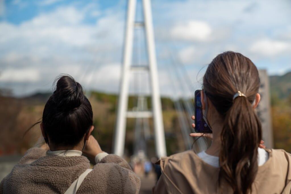 visiteur photographiant le pont suspendu de kokonoe