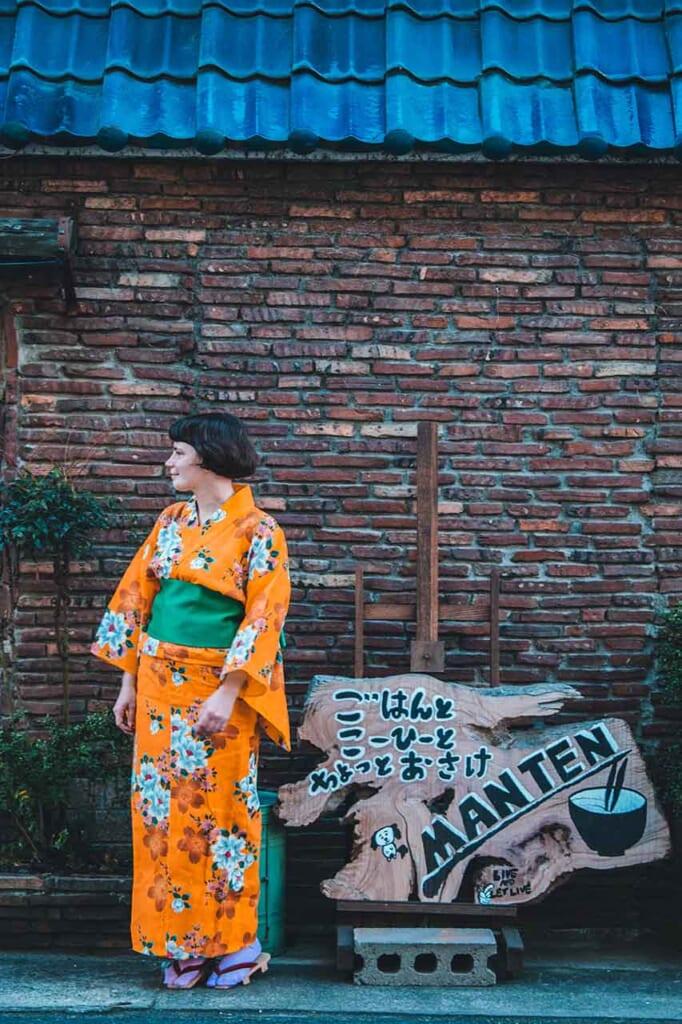 Femme occidentale en yukata orange et vert devant un mur de briques