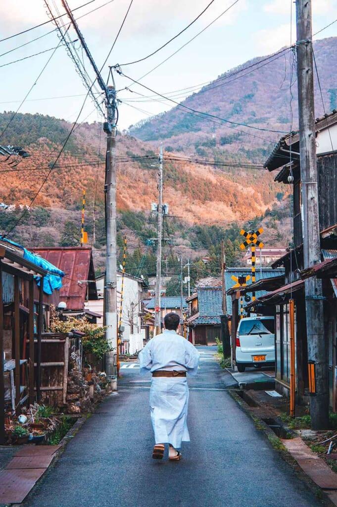 Homme marchant dans un village japonais en yukata