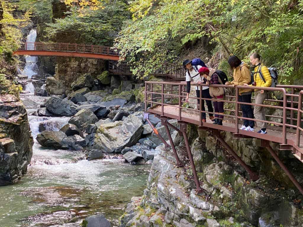 Randonneurs près d'une cascade dans la vallée de Hida au Japon