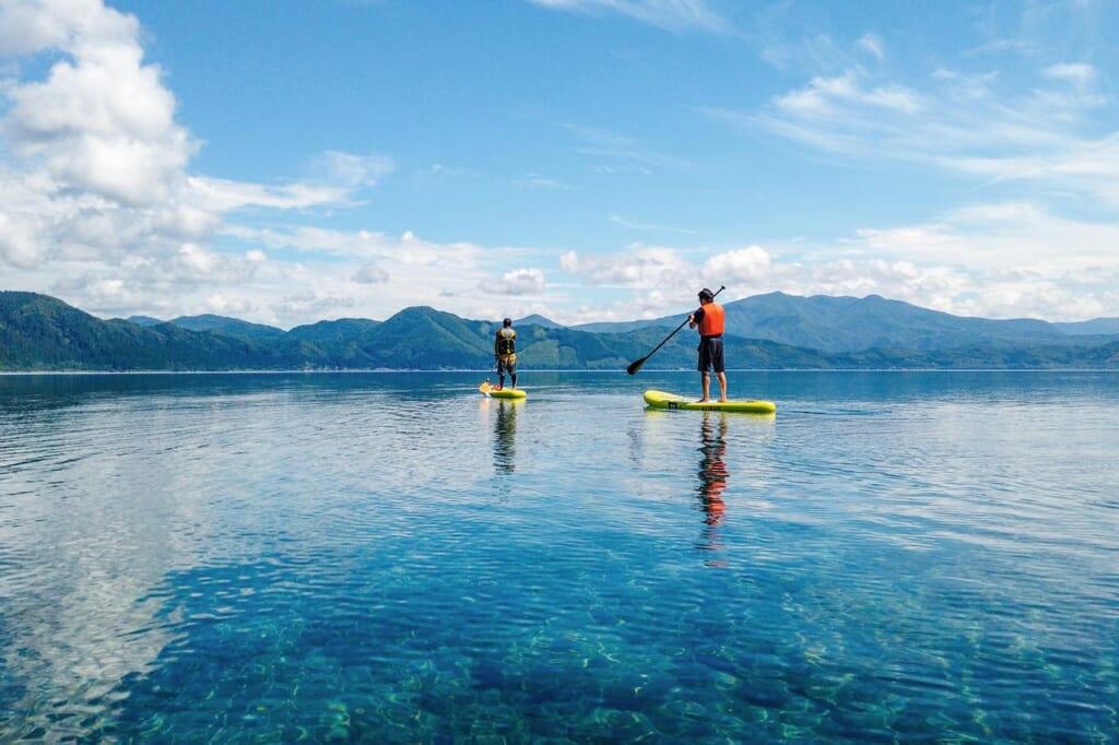 Deux personnes faisant du stand-up paddle sur le lac de Tazawako à Semboku