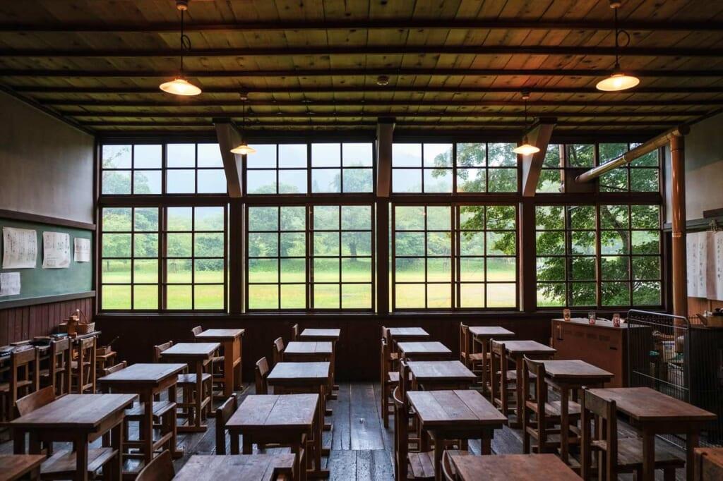 Salle de classe d'une ancienne école japonaise à la campagne, avec des pupitre des bois et un harmonium