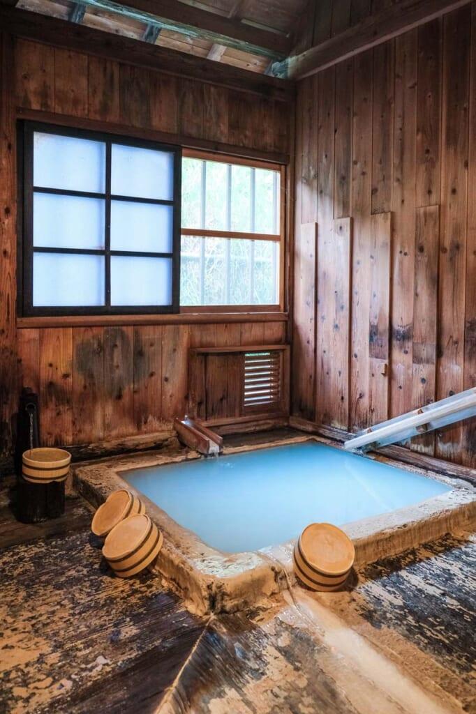 Onsen bleu laiteux en intérieur, dans un bâtiment en bois