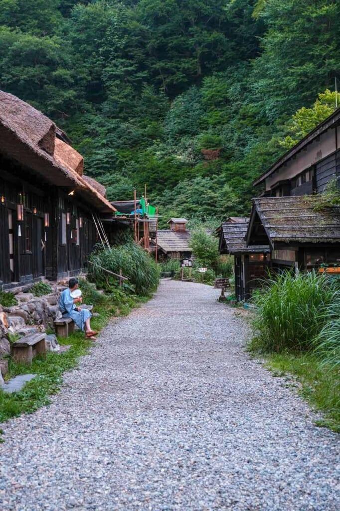 L'allée de Tsurunoyu Onsen à Nyuto, bordée de bâtiments en bois au toit de chaume