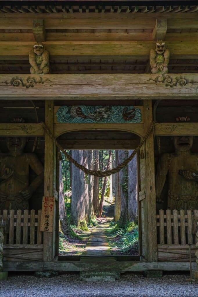 Porte Niomon ouvrant sur une allée bordée de cèdres, dans un santuaire japonais