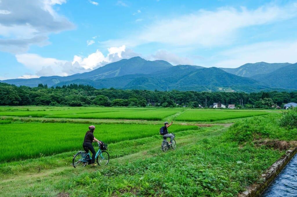 Personnes à vélo dans la campagne japonaise : rizières et montagnes