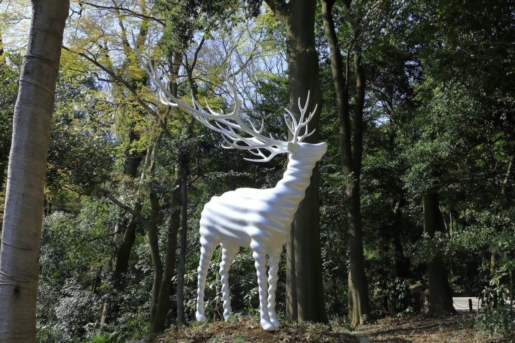 sculpture d'un cerf blanc en forêt