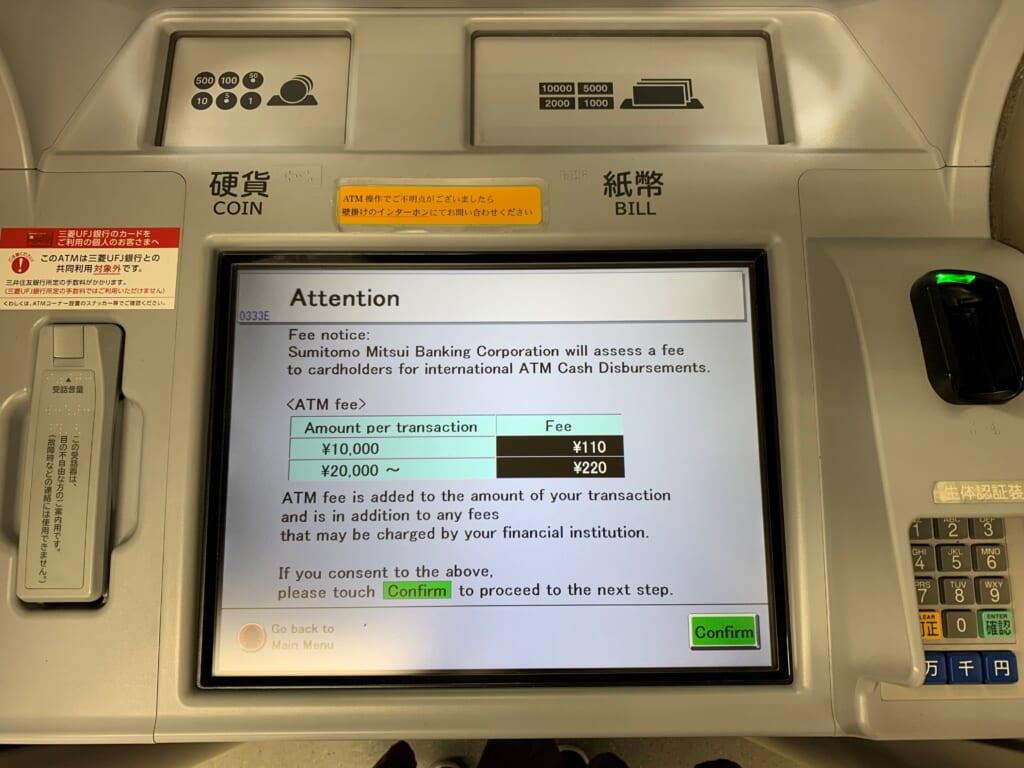 écran d'un distributeur au Japon indiquant les frais de retrait