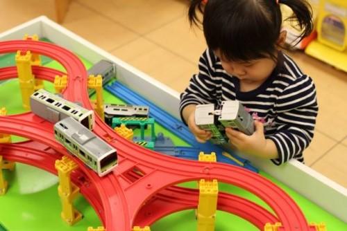 Niña jugando con trenes de juguete en Japón