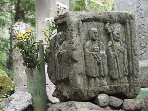 Roca esculpida y ramo de flores en Kumano Magaibutsu (Kunisaki, Oita)