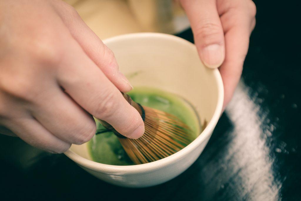 Removiendo el té matcha con la barilla de bambú