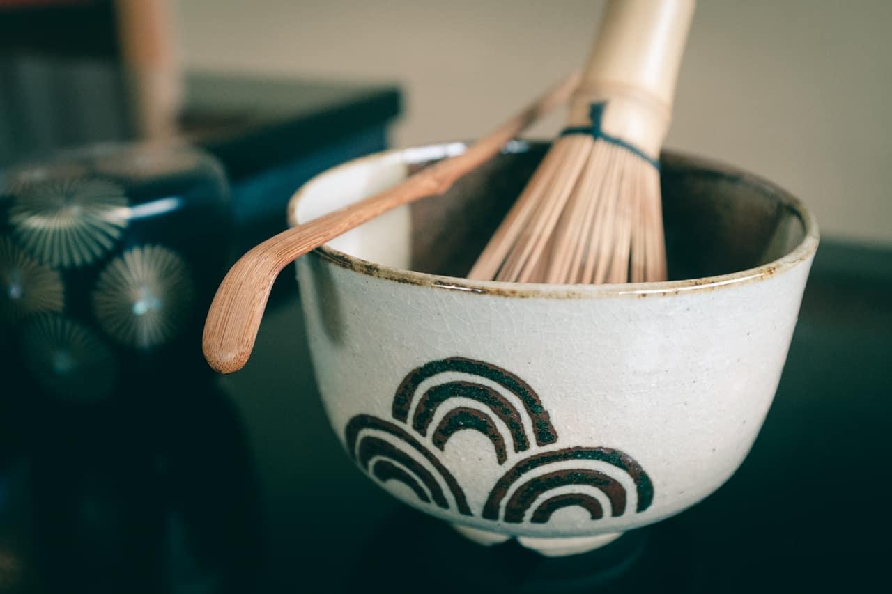 Una taza de té con el batidor del bambú