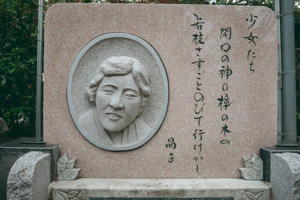 Una piedra con la cara y un texto de Akiko Yosano