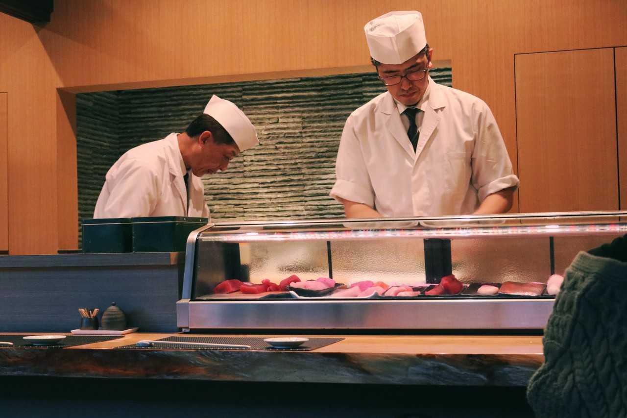 Los cocineros con el pescado fresco