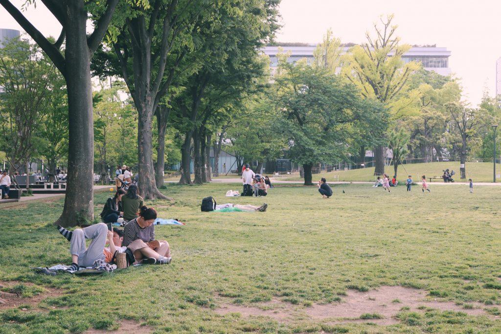 Gente disfrutando del buen tiempo sentados en la hierba en Shiki no Mori