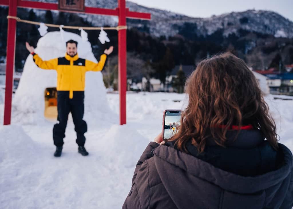 Maria y Hernán sacándose fotos delante del santuario de nieve en Iiyama
