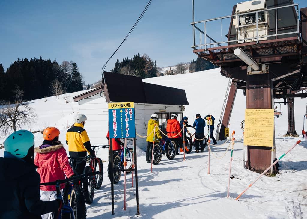 Fila de personas subiendo el telesillas para hacer snow cycling