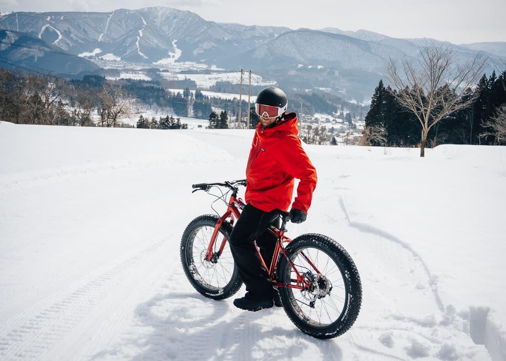 Uno de nuestros compañeros de snow cycling a punto de bajar la bajada con las bicis de nieve