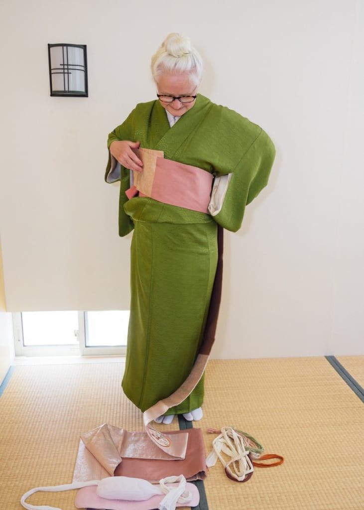 Gira hacia las agujas del reloj mientras estás de pie agarrándote el obi