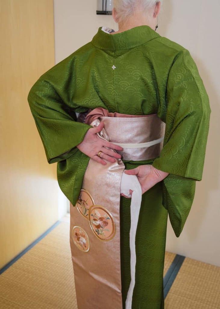 Poniendo el obi-makura con una mano mientras agarras el obi con la otra
