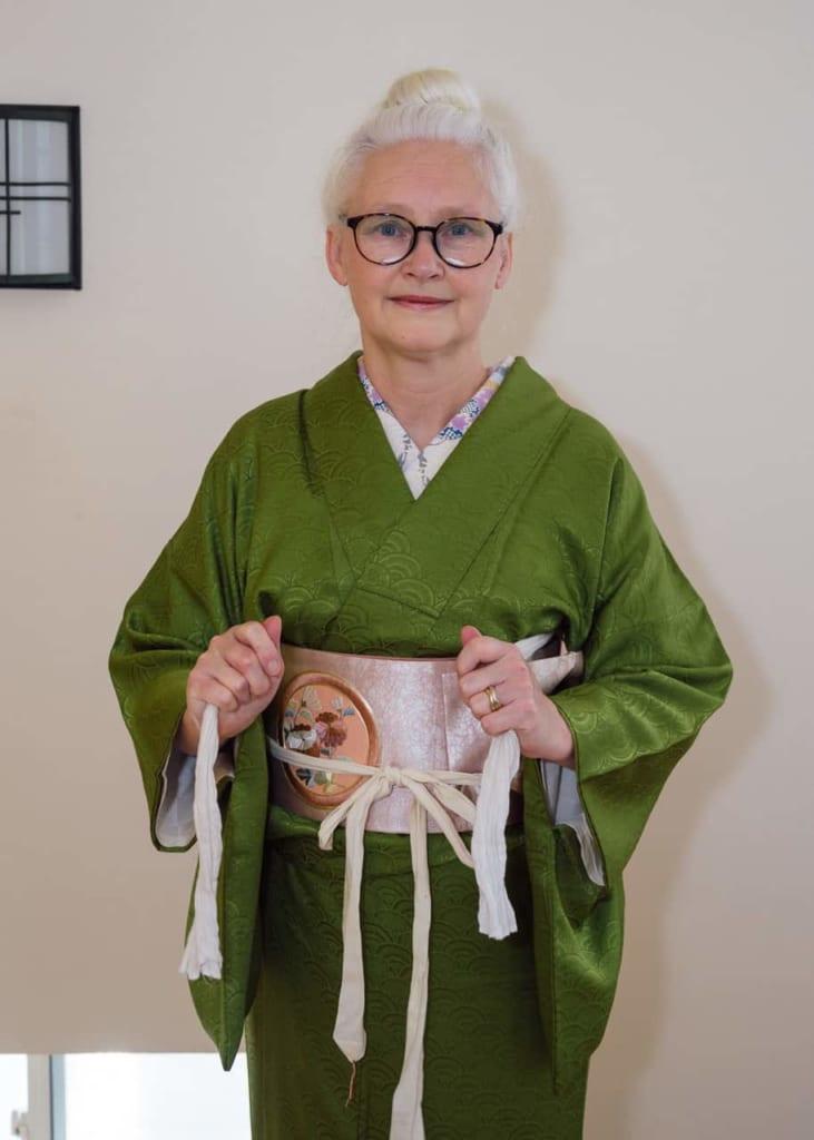 Agarrando las tiras del obi-makura por delante