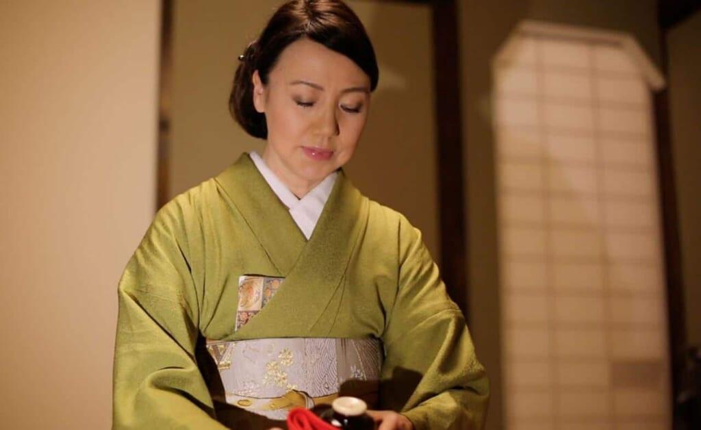 Una mujer con kimono haciendo la ceremonia del té