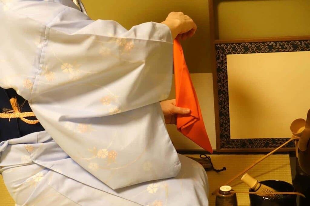 Mika pliega y despliega varias veces el fukusa durante el taller de la ceremonia del té en Tokio