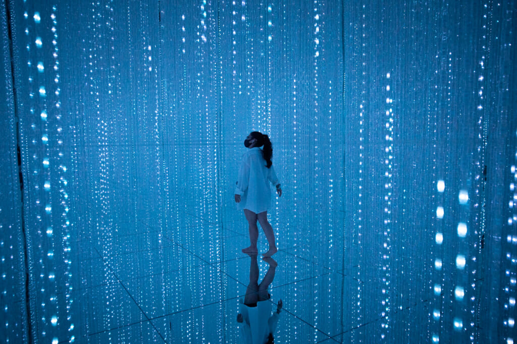 chica caminando maravillada entre cristales de luz azules